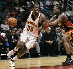 Atlanta Hawks forward Shelden Williams drives against Golden State Warriors forward Josh Powell in the second half of their NBA basketball game in Atlanta