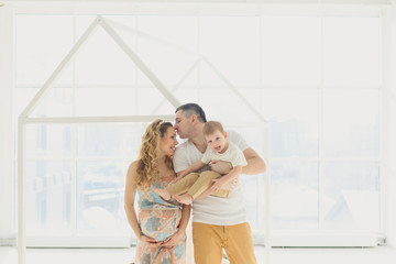 Happy Family: Pregnant mother with father and little boy, Against the window in a bright room