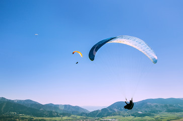Flying paragliders in sky