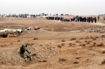 Iraqi villagers troop to a voting center to cast their vote for the national polls in Al Anbar ...