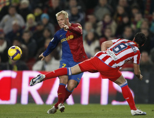 Barcelona's Gudjohnsen fights for the ball against Atletico Madrid's Garcia during their Spanish King's Cup soccer match at Camp Nou stadium in Barcelona