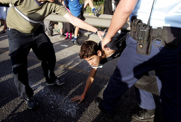 Israeli police officers scuffle with a demonstrator blocking a main road near Tel Aviv.