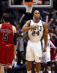 New Jersey Nets forward Jefferson reacts next to Chicago Bulls Nocioni after he scored a three-pointer in the overtime period of their NBA basketball game in East Rutherford