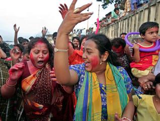 Hindu women dance after the immersion of Hindu goddess Durga in the Ganges river in Kolkata