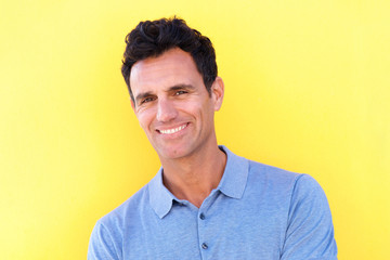 handsome man smiling against yellow background