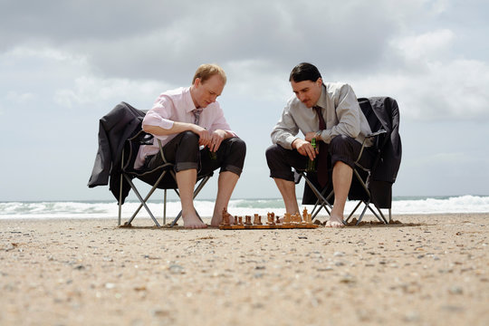 Businessmen playing chess on beach