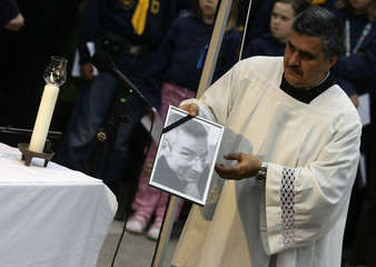A priest carries the picture of Dominik Brunner on a railway platform at the train station of the Munich suburb of Solln