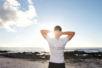 man looking at sea with hands behind head