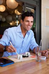 businessman sitting at restaurant eating sushi