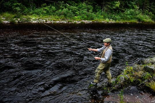 Fly fisherman in Margaree River, Cape Breton Island, Nova Scotia