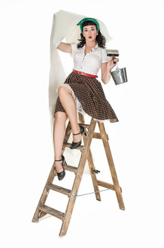 Young woman sitting on stepladder with wallpaper, 1950s style