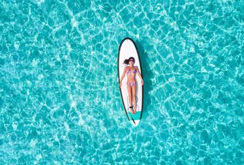 Attraktive Frau im Bikini sonnt sich auf einem Surfbrett über dem türkisen Wasser der Malediven