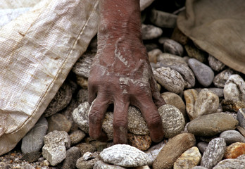 An Indian labourer takes a handful of rocks to crack on the banks of the Mahananda river in Siliguri.