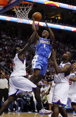 Nuggets guard Billups shoots between the defense of the 76ers Dalembert and Brand during the fourth quarter of NBA basketball action in Philadelphia