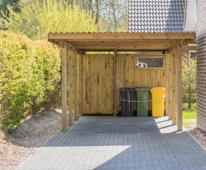 Carport aus Holz mit Mülltonnen