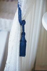 blue brush wings on a white lace curtain.The ease and tenderness