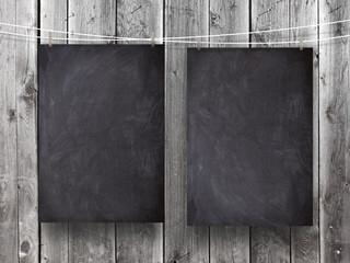 Two blank blackboard frames against gray wooden boards background