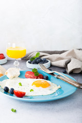 Fried egg on blue plate, tomatoes, blueberries, mint tea and orange juice. Healthy breakfast concept with copy space.
