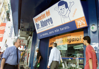 ARGENTINES WALK PAST A DRUGSTORE IN BUENOS AIRES.