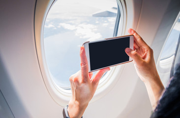 Close up woman hand holding mobile phone and take a photo outside airplane window,Blank screen for adding your design