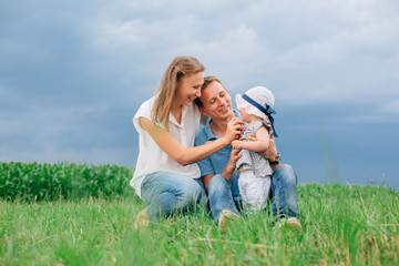 Young family in jeans sitting on the grass having fun together. Little girl in panama hat.
