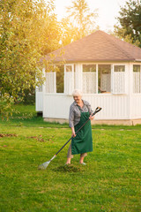 Lady with rake in garden. Woman in apron working. How to care for nature.