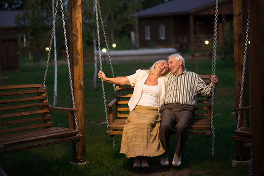 Man and woman, porch swing. Senior couple smiling outdoor.