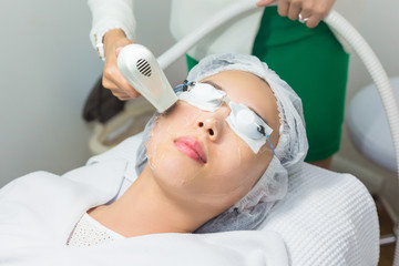 Close-up of Beautician Giving Laser Epilation Treatment To Young Woman Face.