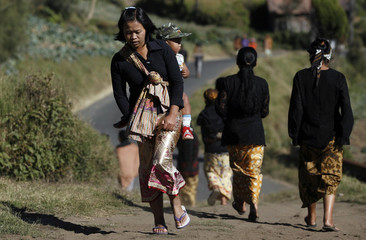 A woman from the Tengger tribe walks to a polling station to place her vote in Ngadisari village in East Java province