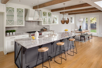Kitchen with Lights Off in New Luxury Home with Large Island, Hardwood Floors, Range Hood, and Glass Fronted Cabinets, Horizontal Orientation