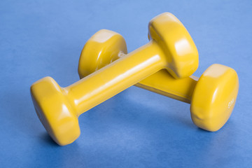 Pair of yellow dumbbells on a blue surpface.