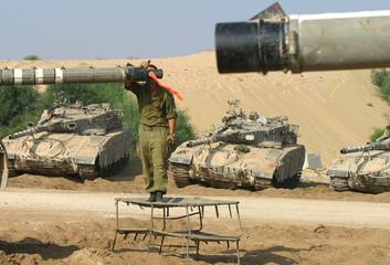 ISRAELI SOLDIER ADJUSTS HIS TANK'S GUN AT EREZ CROSSING INTO THE GAZASTRIP.