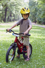 Child boy on a bicycle in the forest in summer. Boy cycling outdoors in safety helmet. Sun flare effect added