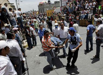 People and paramedics carry a man who was injured during a running of the bulls in Huamantla