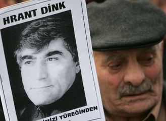 A man holds a portrait of Turkish Armenian editor Dink during a protest outside Turkey's embassy in Brussels