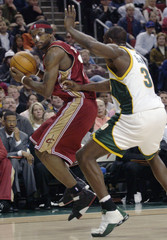 Cleveland Cavaliers LeBron James looks to drive around Seattle SuperSonics Reggie Evans.