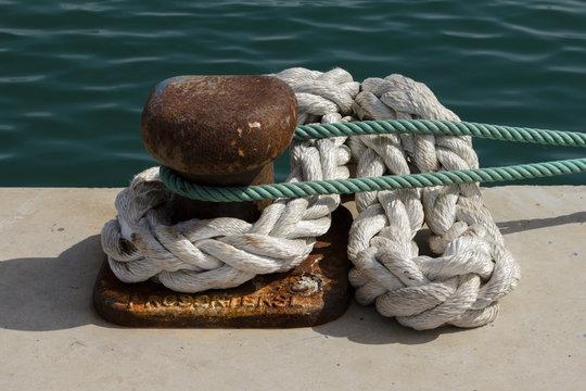 Noray con cuerdas en puerto pesquero.