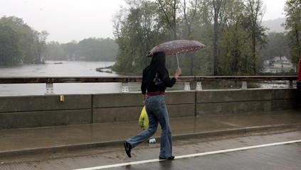 A woman returning from her shopping walks on a bridge over the flooding Ramapo River to her flooded neighborhood in New Jersey