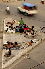 A group of homeless Indians rest on a pavement in New Delhi