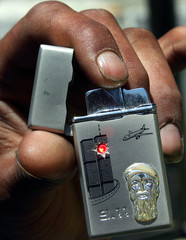 Palestinian man holds cigarette lighter with engraved face of Osama bin Laden and airplane about to ...