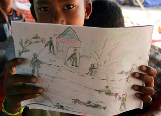 An Acehnese child Yuliandi Saputra shows his drawing of a conflict scene at Lhok Nga village.