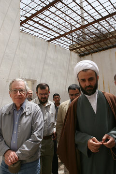 Academic and linguist Noam Chomsky walks next to with Hizbollah official Sheikh Nabil Kawook in south Lebanon