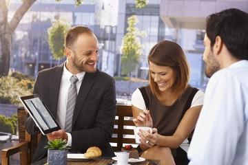 Happy businessman doing presentation at breakfast