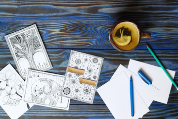 Many postcard in doodling style with drawn picture, pencils, pen and ceramic cup with tea lemon on wooden blue background. Hand drawn, creativity, humor, ideas. Place for inscription