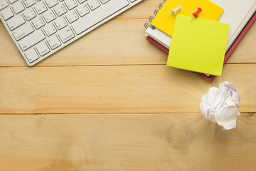 top view. post-it note putting on top of notebook and have garbage paper, keyboard putting beside it. wooden background. this image for business and education