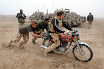 Britain's Prince Harry pushes as a soldier tries to start an abandoned motorcycle in Helmand province, southern Afghanistan
