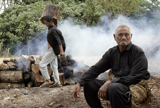 A village elder looks on as an 'umu', an underground oven, is prepared to cook meals for the people attending the king's funeral in Nuku'alofa, Tonga