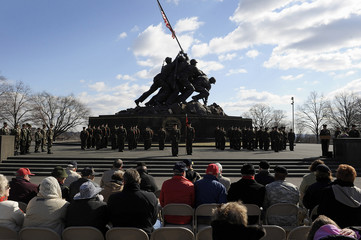 People attend a ceremony in honor the 64th anniversary of the raising of the US flag on the island of Iwo Jima during World War II, at the Marine Corps War Memorial in Arlington, Virginia