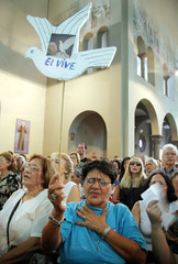 A woman holds up a paper dove with a picture of the Pope John Paul II during a mass in Caracas.