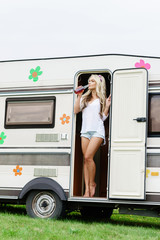 Young and beautiful hippy girl standing in trailer's door. Holiday, journey, vacation concept.
